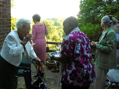 Guests, including Marjorie, enjoy a drink and a lovely view.